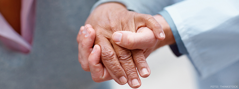 Nursing staff holding elderly patients hand